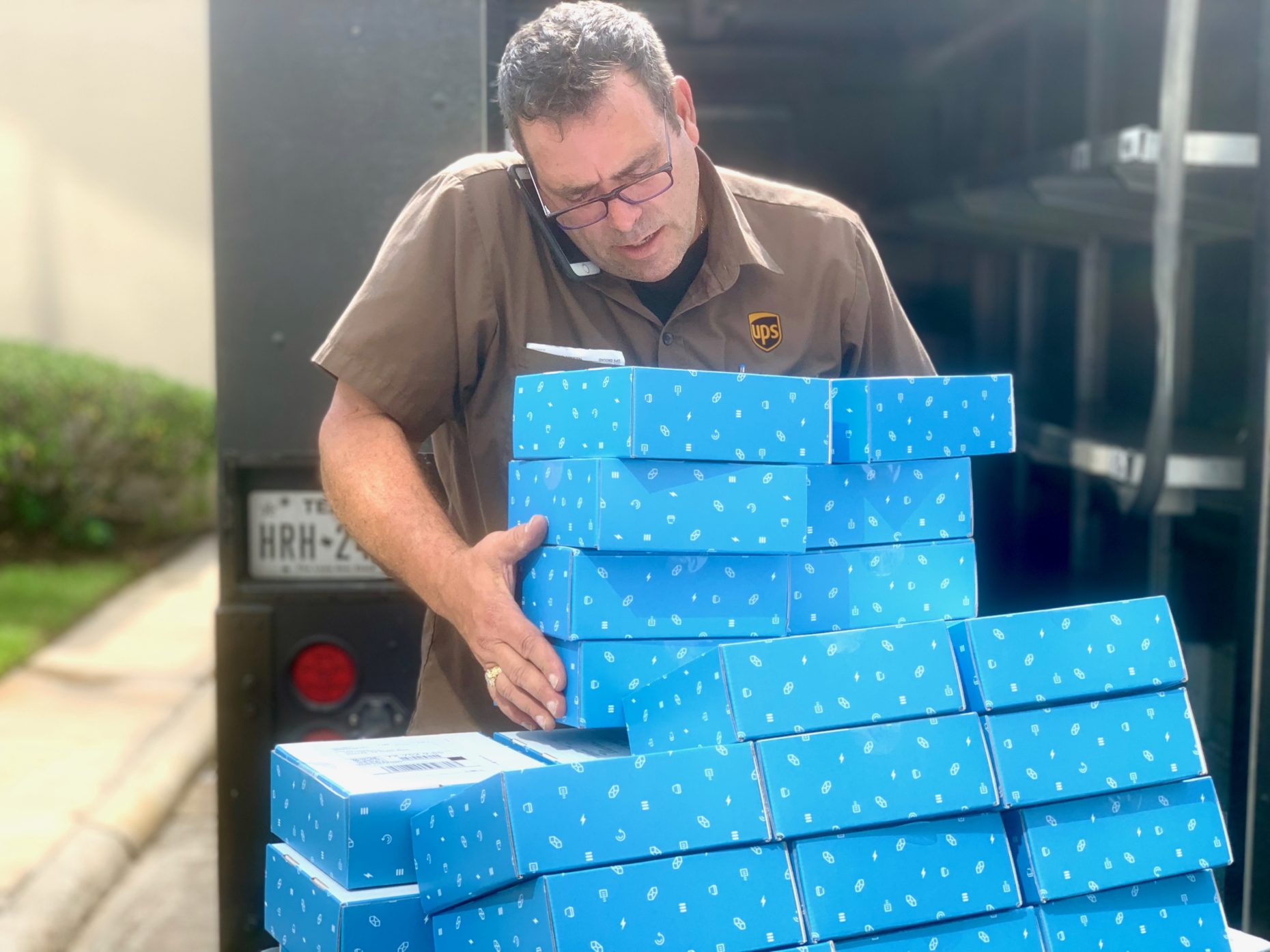 UPS guy picking up a lot of blue boxes.